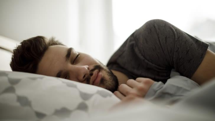 Junger Mann liegt im Bett mit geschlossenen Augen und einem zufriedenen Gesichtsausdruck.