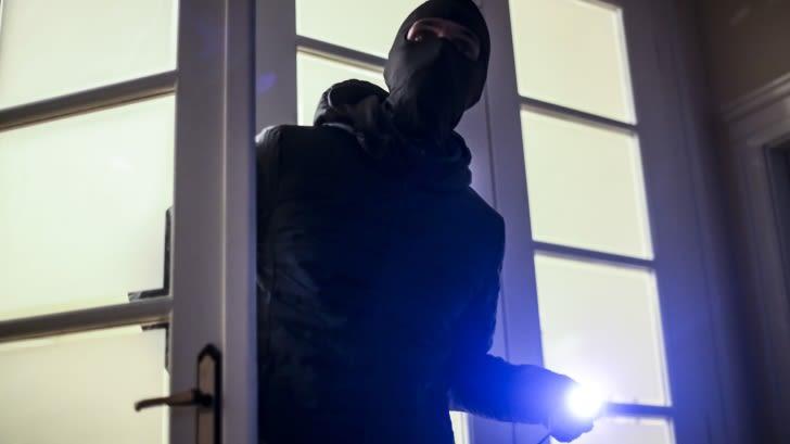 Maskierter Mann mit Taschenlampe in der Hand betritt eine Tür.
