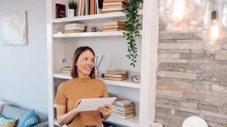 Frau mittleren Alters steht in einem Wohnzimmer und hält ein Tablet in der Hand. Sie blickt mit zufriedenem Blick auf ihre Deckenbeleuchtung und tippt auf ihrem Tablet.