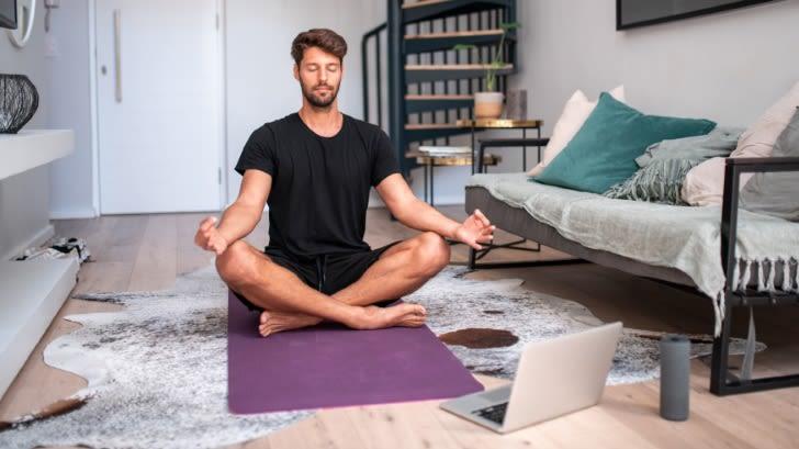 Junger Mann sitzt in seinem Wohnzimmer auf dem Boden auf einer Yogamatte. Er sitz im Schneidersitz, seine Hände ruhen auf seinen Knien. Er hat die Augen geschlossen. Vor ihm steht ein Laptop.
