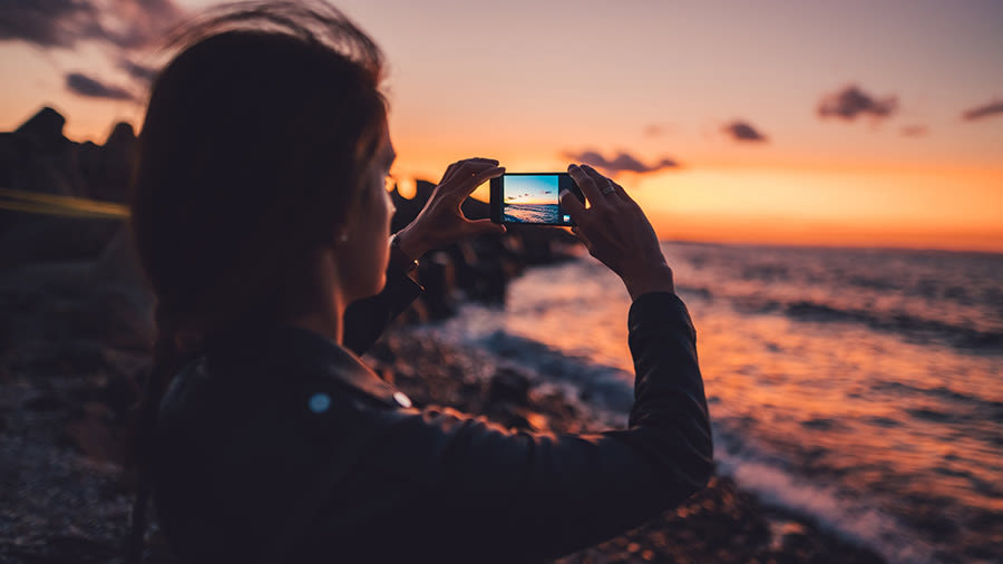 Frau mit Handy/Smartphone am Strand