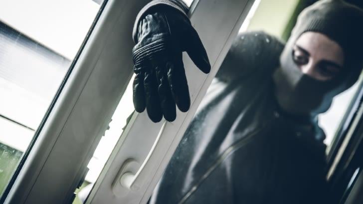 Ein maskierter Mann mit Handschuhen greift in ein gekipptes Fenster.