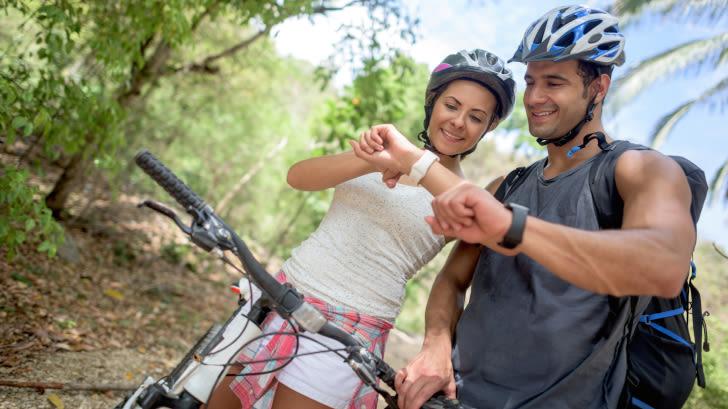 Zwei FahrradfahrerInnen schauen auf ihre Fitness-Uhren
