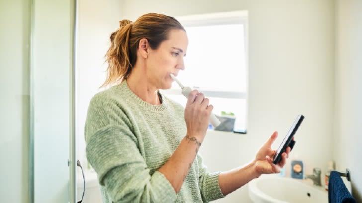 Frau steht im Badezimmer und putzt sich mit einer elektrischen Zahnbürste die Zähne. Sie hält ihr Smartphone in der Hand und schaut darauf