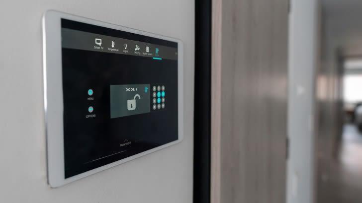 Ein Bildschirm, etwa so groß wie ein Tablet, hängt neben der Eingangstür. Über diesen Bildschirm lassen sich Überwachungskameras, Alarmanlagen und alle Elemente, die zu Smart Home Sicherheit gehören, bedienen.