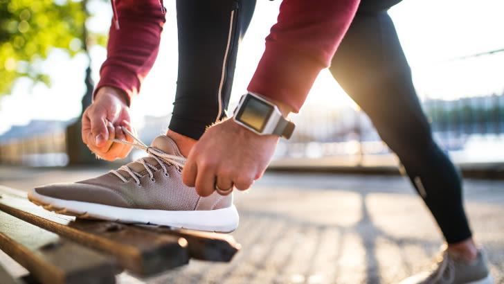 Mann mit Smartwatch schnürt seinen Schuh