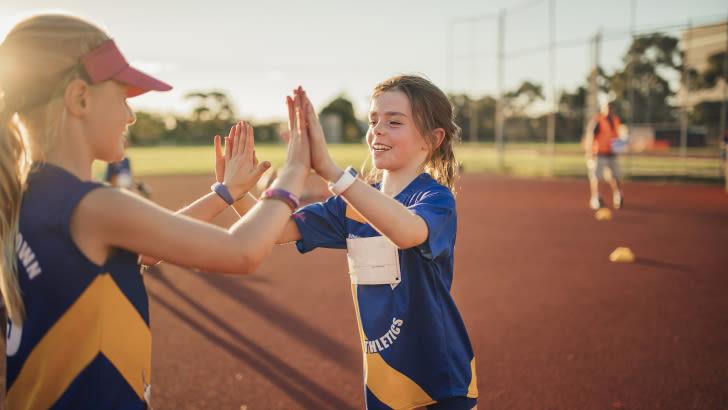 Zwei Mädchen mit Fitness-Trackern klatschen sich ab